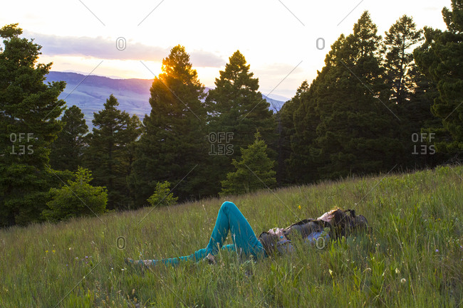 A woman lays in meadow in Montana's Rocky Mountains