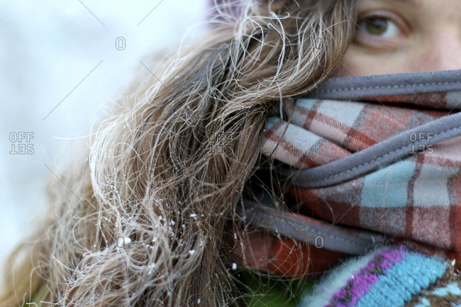 Woman with frosty hair wrapped up in a colorful scarf during winter in Montana