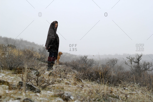 Woman stands facing into blustery winter storm in Idaho