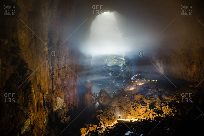 A cave explorer illuminates a large cave passage in Hang Son Doong