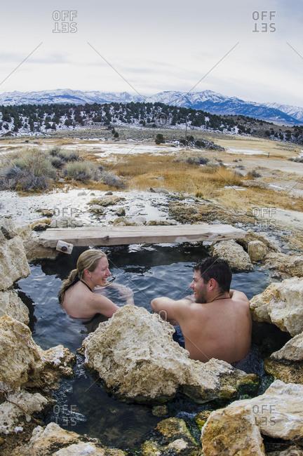 Couple soaks in winter at Travertine Hot Springs, Eastern Sierras, California