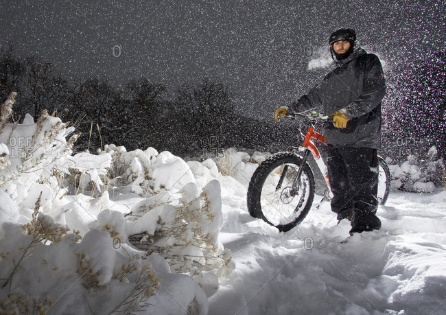 Man stands with fat tire bike while heavy snow falls