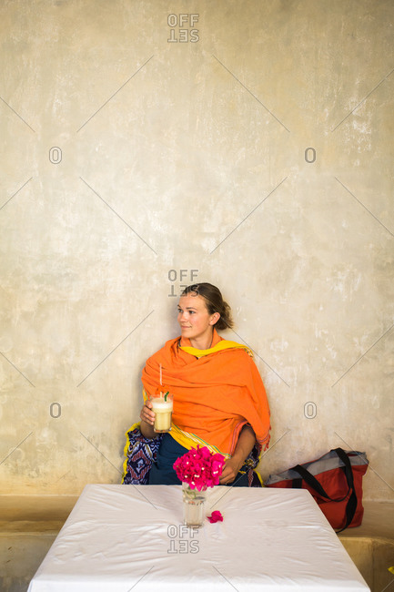 A young woman in shawl sits with fruit drink in hand