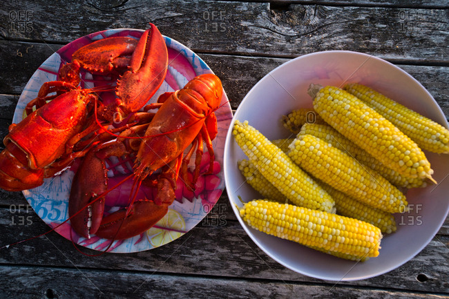 Corn on the cob and cooked lobster on a picnic table