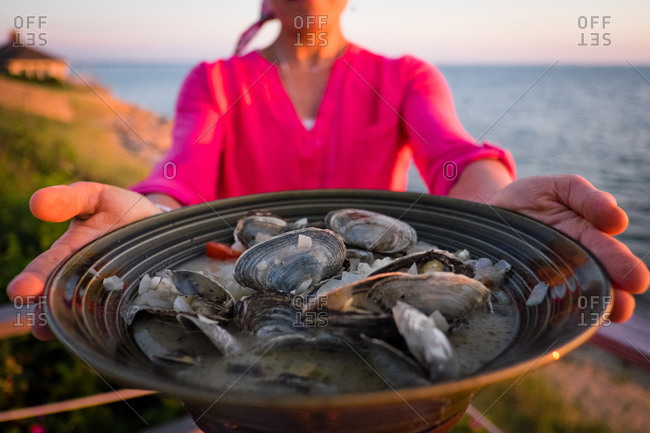 Woman holding a bowl of clams on Cape Code, MA