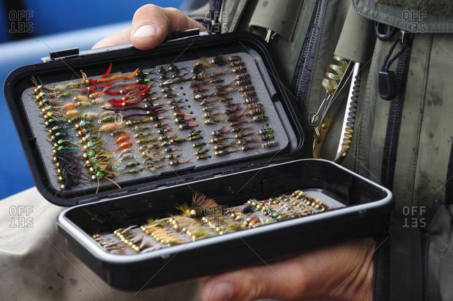 A fly fisherman examines his fly box