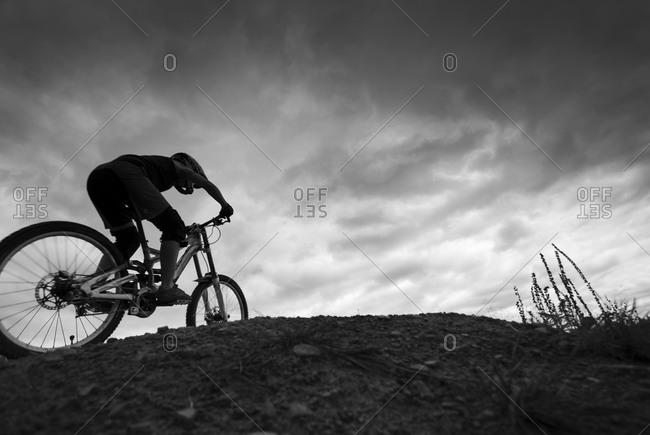 Female downhill mountain biker riding course