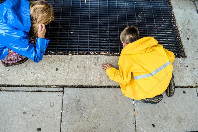 Girl and boy peer in sidewalk vent in Washington, DC