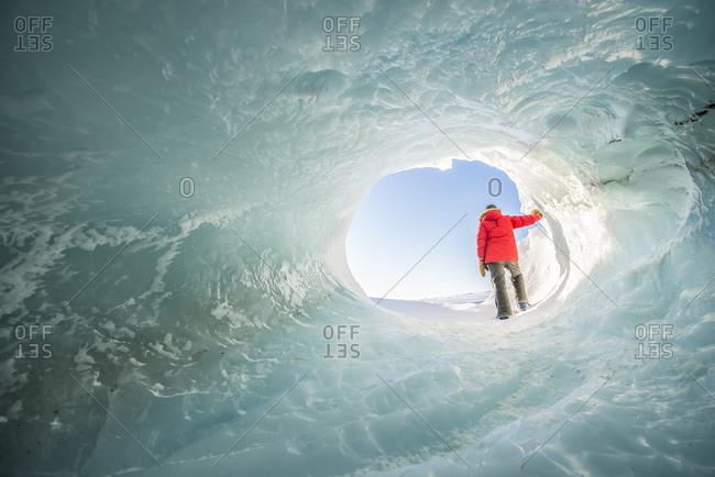 Woman explores a tunnel in iceberg in Antarctica