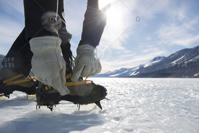 Man straps on crampons on a glacier in Antarctica