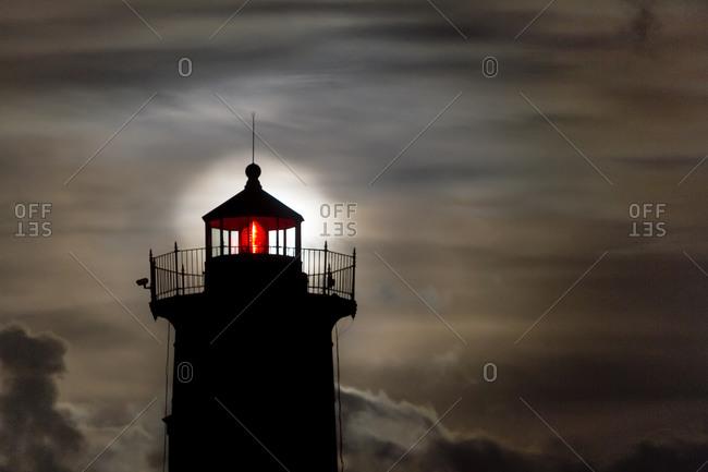 Moon creates a halo behind lighthouse in Cape Neddick, Maine