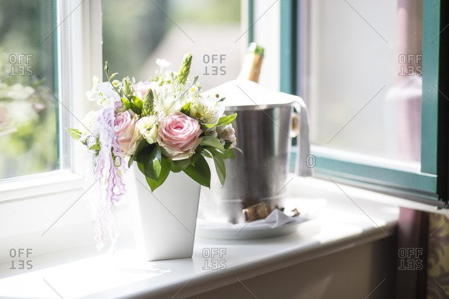 Bridal bouquet and wine cooler on window sill