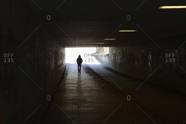 Person walking in tunnel - Offset
