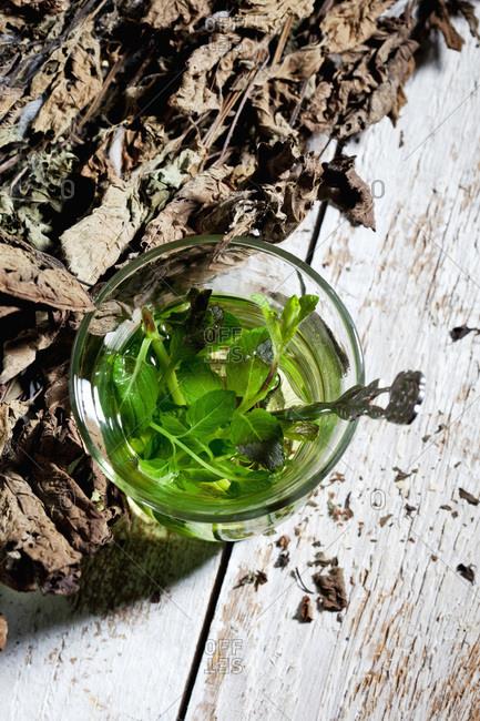 Tea glass of fresh pepper mint tea and dried pepper mint on wood