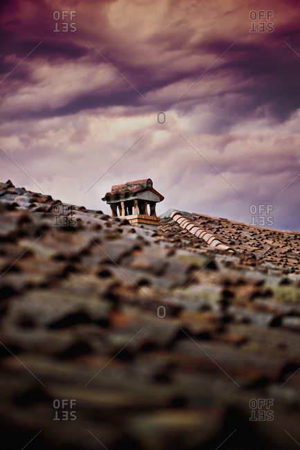 Cloudy and stormy sky over ancient shingle roof