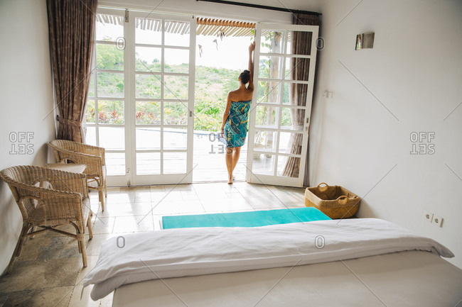 Woman standing at opened terrace door of a holiday villa, Bali