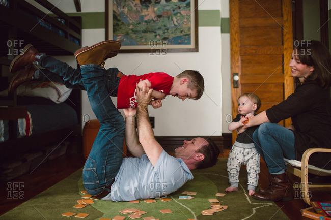 Parents goofing around with children in bedroom
