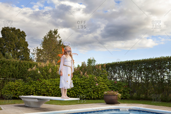 A girl in an angel costume stands on a diving board