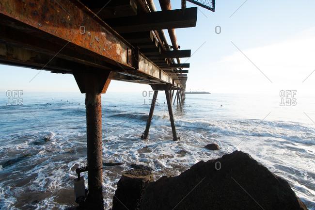 Surfers under a pier in Ventura, California