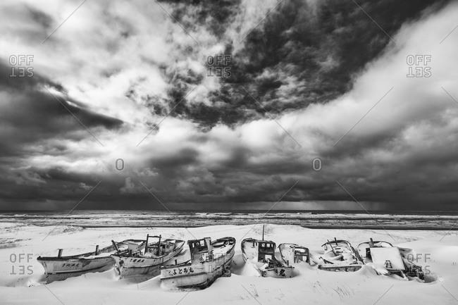 Hokkaido, Japan - January 11, 2015: Boats on snowy Japanese beach