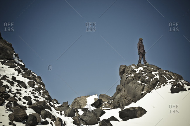 Man on rocky peak in Chilean mountains