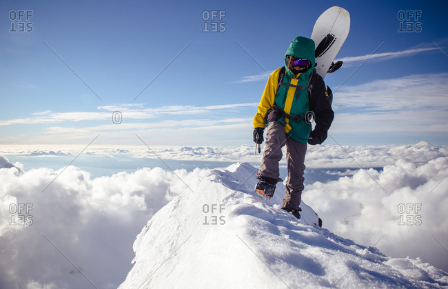 Hiker carrying snowboard on high Chilean mountain ridge