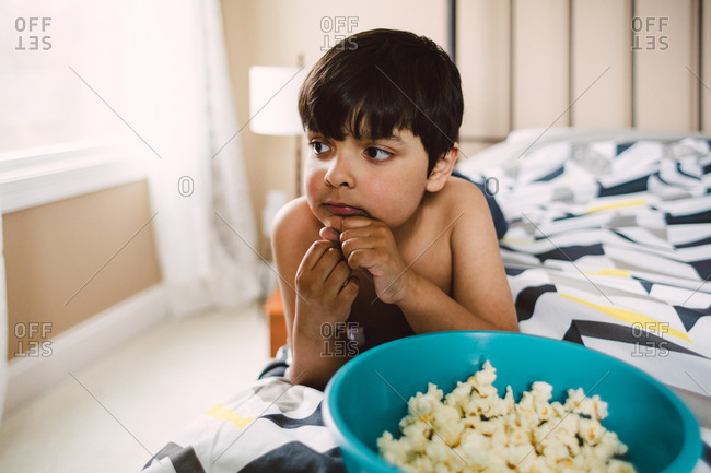 Boy laying on bed with bowl of popcorn