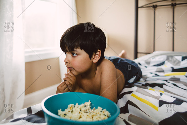 Boy lying on bed with bowl of popcorn