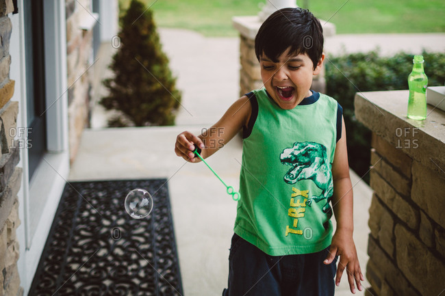 Boy yelling while blowing bubbles on porch
