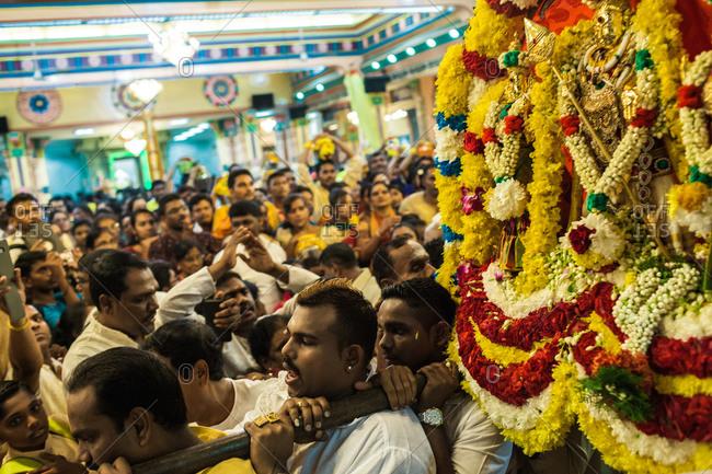 Kuala Lumpur, Malaysia - January 1, 2013: Tamil devotees carry the image of Lord Murugan in Sri Mahamariaman Temple in Kuala Lumpur, Malaysia