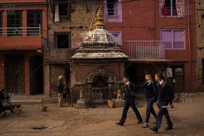 Bhaktapur, Nepal - November 17, 2014: Young boys walking back home after school in Bhaktapur, Nepal