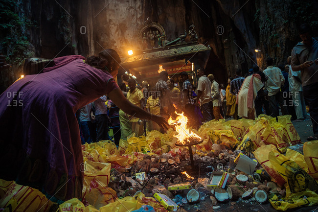 Batu Caves, Kuala Lumpur, Malaysia - January 27, 2013: A woman throws an offer into the fire in front of the Sri Maha Mariamman Temple, at the very end of the pilgrimage of the Thaipusam