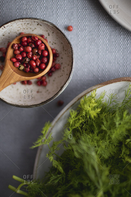 Close up of red peppercorns and fresh dill