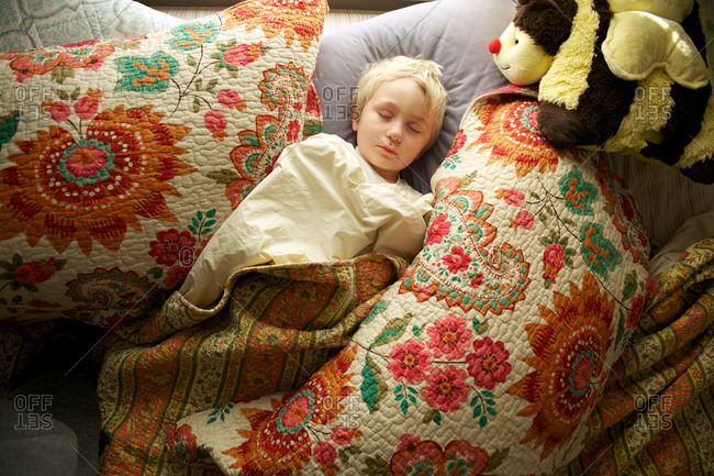 A little boy sleeps while wrapped in a large quilt
