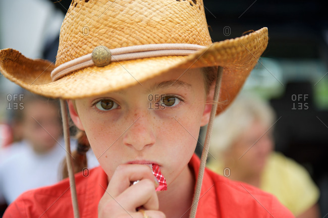 A little girl in a cowboy hat chews on candy