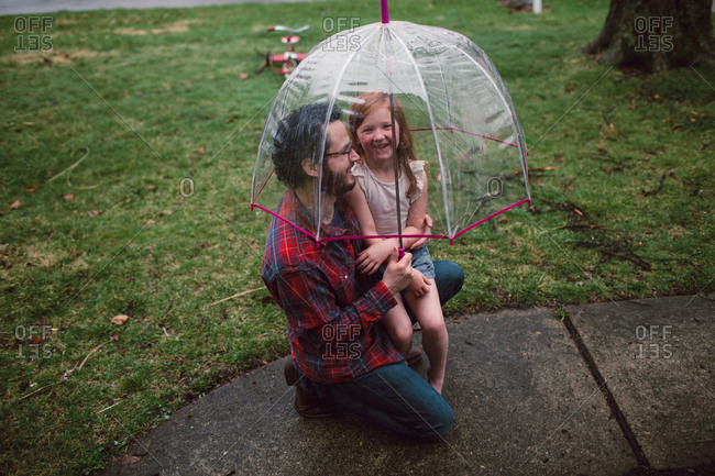 A little girl and her dad giggle under a bucket umbrella
