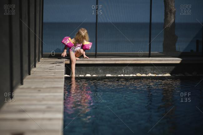 Girl in water wings climbing into pool