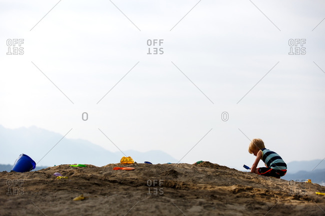 Boy playing on a mound of sand with pail and shovel