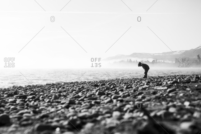 Child bending down at the edge of the water on a rocky beach