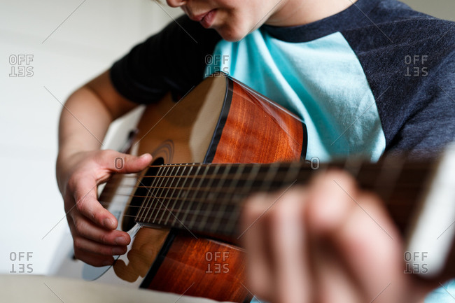 Young boy strumming the strings of his guitar