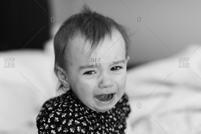 A baby cries on a bed