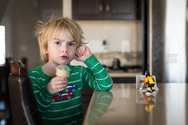 A little boy with furrowed eyebrows eating ice cream