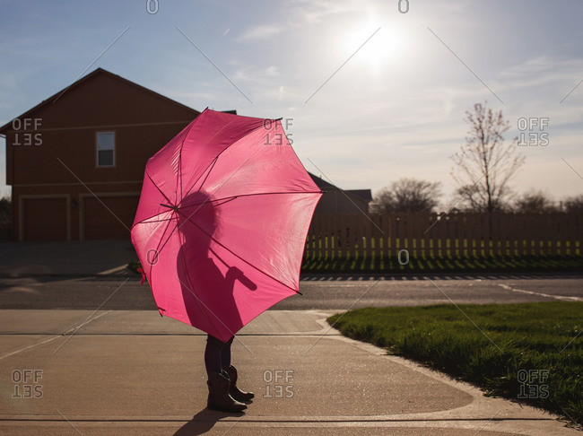 Young girl holding a pink umbrella on a street