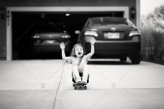Young girl skateboarding on a driveway