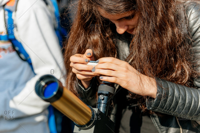 Strasbourg, France - March 20, 2015: Young woman photographing with a mobile device a solar eclipse through filtered telescope in the Place du Chateau
