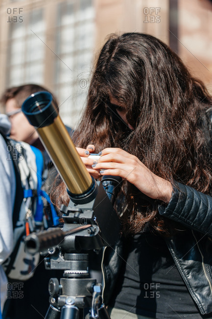 Strasbourg, France - March 20, 2015: Young woman viewing a solar eclipse through a filtered telescope