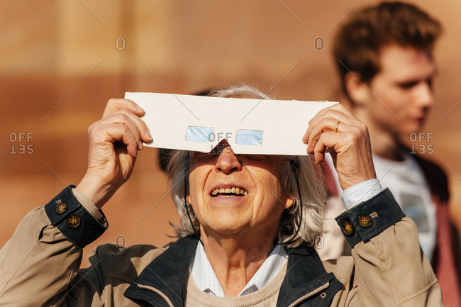 Strasbourg, France - March 20, 2015: Senior woman looking at sky with protective glasses to watch solar eclipse