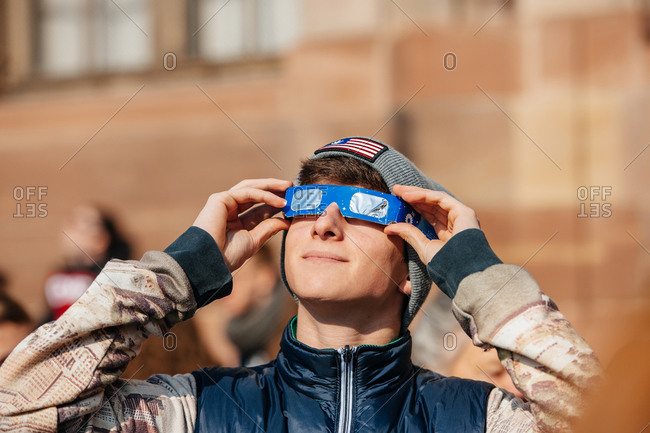 Strasbourg, France - March 20, 2015: Boy happily watching solar eclipse with special protective eyewear