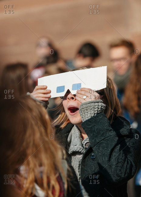 Strasbourg, France - March 20, 2015: Amazed woman watches a solar eclipse through protective glasses