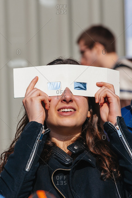 Strasbourg, France - March 20, 2015: Young woman watching a solar eclipse through protective glasses